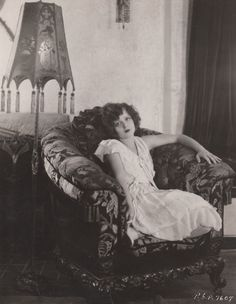 Clara Bow basking in the glow of her awesome home furnishings circa 1927.  Stamped on reverse: CLARA BOW in Paramount Pictures