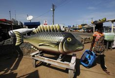 A street vendor passes a coffin made in the shape of a fish at the workshop of Kane Kwei in the Teshi area of Accra, Ghana May 16, 2013. REUTERS/Luc Gnago