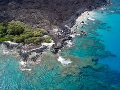 An aerial view of ocean water bordered by a rocky and green brush coastline in Hawaii.