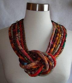 One of a kind seven fabric cord necklace tied in a knot with cowrie shells at shoulder. This necklace combines batiks with African fabrics, the ties allow you to make it the length that compliments your outfit. Its sure to be complimented when worn.    Double thread hand stitching used to ensure durability.    From a smoke free home.  Shipping to USA only