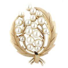 Vintage spilla TRIFARI  Questa spilla vintage della Trifari è un classico esempio di gioielli vintage americani degli anni 60. Il gioello è a motivo floreale decorato con perline bianche. Perfetto stato di conservazione quindi adatto sia per collezione che da indossare
