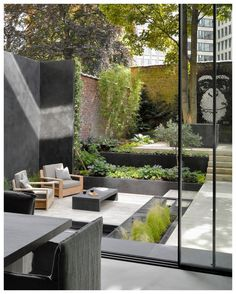 Two Century Homes In Belgium Were Combined Into One And Given A Contemporary Update This modern garden has been landscaped with various levels, creating places for the home owners to relax in the lounge, or take in the mural on the back brick wall. Modern Garden Design, Contemporary Garden, Patio Design, Landscape Design, Contemporary Homes, Modern Courtyard, Modern Patio, Home Design, Back Gardens