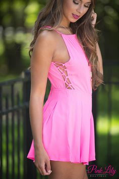 This vibrant romper is perfect for a day at the county fair or relaxing with friends! It features a gorgeous shade of pink, a high neckline in front, and a low-cut back for a stunning start. There's even more gorgeous details, with two cutouts on each side with lace up details on each side and a unique style of adjustable halter-style top with a fabric tie in back! The skirt is bouncy and slightly pleated with a zipper in back.