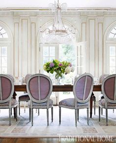 Luxurious Louis XVI Dining Room… Why it makes us swoon: Who knew we could get so excited about paint? But this paneled presentation – a month-long process that started with a blue base topped with beige strie that was then trimmed with silver leaf atop gold -- boasts the quintessential Louis XVI look. An elaborate chandelier sparkles up above, while arch-topped French doors offer a view of the lush landscaping in the terrace and garden. (such an elegant feeling to the room)