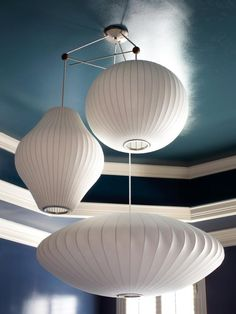 A trio of white pendant light shades in assorted shapes creates a focal point against a blue ceiling, seen on HGTV.com.