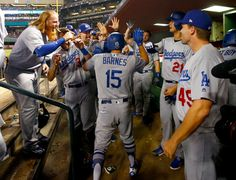 October 9, 2017:  Dodgers sweep Diamondbacks to reach NLCS for 3rd time in 5 years  - Los Angeles Dodgers' Austin Barnes (15) high fives teammates after hitting a solo home run against the Arizona Diamondbacks during the sixth inning of game 3 of baseball's National League Division Series, Monday, Oct. 9, 2017, in Phoenix. (AP Photo/Ross D. Franklin)