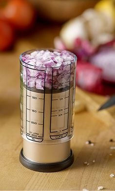 Measuring cup with sliding sleeve to portion out ingredients, works with liquids too.