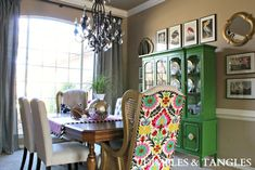 I heart this. The bright colors, the hue of green on that china cabinet, and the framed artwork/mirrors around the cabinet.