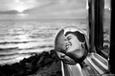 Couple kissing in wing mirror of car, California, 1955. Elliott Erwitt.