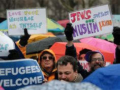 Demonstrators hold up signs during a rally in Battery Park organized by the Hebrew Immigrant Aid Society to mark a National Day of Jewish Action for Refugees, Sunday, Feb. 12, 2017, in New York. (AP Photo/Julie Jacobson)