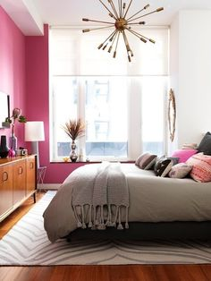 pink walls and a grey bed, lovely windows, pretty pillows, and very pretty dresser