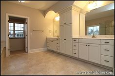 This his and hers master bath leads to a walk in closet with island cabinet.