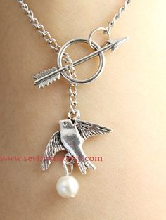 The Hunger Games Inspired Arrow, Mockingjay, and Peeta's Pearl silver necklace, via Etsy.
