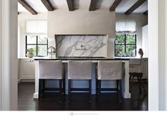 """LOVE the plaster hood with marble backsplash. Love the linen barstools, color scheme, dark floors, like the beams but maybe not if it interferes with Kitchen """"hall"""" flow"""