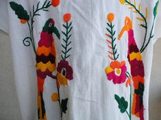 Short sleeve cotton dress with rounded neck. Embroidered birds and flowers. Very colorful in shades of orange, magenta, green, burgundy, & gold. Flat measures approximately Bust 22 inches, Waist 23 inches, Hips 25 1/2 inches. From shoulder to hem 41 inches. No labels.