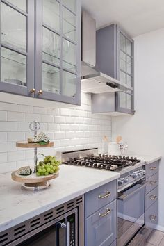 Stunning Ikea kitchen boasts gray glass front upper cabinets and gray lower cabinets paired with honed white marble countertops and a white beveled subway tile backsplash.