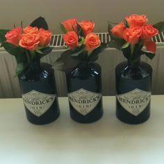 Orange roses in Hendricks Gin bottles