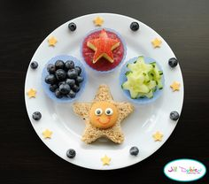 from meet the dubiens blog      Star shaped peanut butter sandwich. Nilla wafer face decorated with icing eyes and food safe markers.    Silicone muffin cups filled with blueberries, unsweetened strawberry kiwi applesauce with an apple star and star shaped cucumbers.    Blueberries and star shaped cheese around the plate.