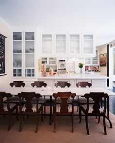 Kitchen Photo - Antique wood chairs surrounding a sleek marble table. Cabinets above peninsula. Lonny