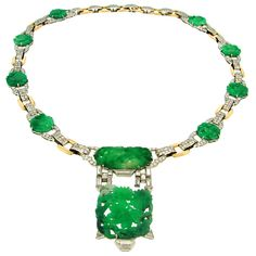 J.E.CALDWELL & Co Carved Jade, Diamond, Platinum & Gold Necklace  USA  Circa 1920's  Elegant Art Deco necklace created by J.E. Caldwell & Co. in the 1920's. It features finest detailed carving on green jade medallions accentuated with baguette and single cut diamonds. Setting is made of platinum and yellow gold.
