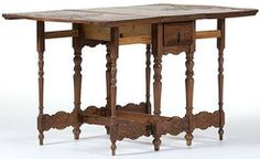 furniture, Spain, Furniture: A Spanish Colonial Revival table, Spanish, 19th century. A walnut with pine secondary, Spanish Colonial Revival gate-leg table with two leaves. A rectangular scrubbed top, skirt below contains a drawer at each end with iron drop pull, followed by turned legs. Decorative carved drawers, apron, and shaped stretcher boards. Also, crown atop an elaborate scroll design carving on the scallop shaped leaves. Legs for leaf supports move on iron hinges.