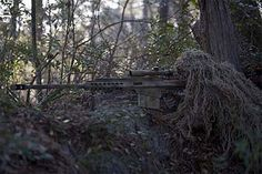 A MARSOC sniper, armed with a Barrett M82 .50 sniper rifle. The sniper is wearing a Ghillie suit, a type of camouflage clothing made to resemble foliage.