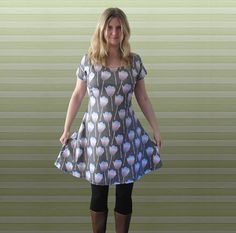 Rainbow tulip dress  This dress is cut from two pieces of fabric to give it a gentle flattering slope to the shoulders and short sleeves. Its designed in a fit and flare shape giving definition to the waist and flattering a curvy figure. The material has the sheen associated with sublimation printing and a soft feel but is opaque and strong enough to cling to the body without losing its shape or becoming see through.  --------------------------------------- Process: Each pattern and print is…