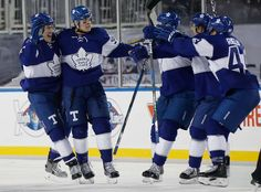 Maple Leafs vs. Red Wings - 01/01/2017 - Toronto Maple Leafs - Photos  Auston Matthews #34 of the Toronto Maple Leafs is congratulated by teammates Jake Gardiner #51, Matt Martin #15, Connor Carrick #8 and Morgan Rielly #44 after scoring the overtime winning goal