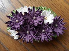 つまみ細工の花のバレッタです。シックな紫と明るい白をコントラストにして制作しました。落ち着いた雰囲気の作品です。大きさは 横 およそ10㎝ 縦 およそ6㎝ くらいです。和装洋装どちらにもお使いいただけると思います。