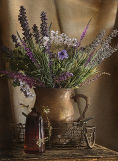 Wire basket, glass, and an old metal? pitcher of wildflowers. Pretty!