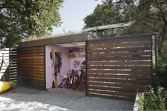Shedbuilt bike shed l Gardenista -- maybe a hybrid: sliding door to open, but narrow along side of building