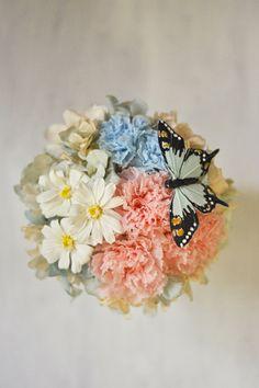 パステルカラーのピンクとブルーのカーネーションと白いジニアの花でふんわり可愛いアレンジメント。やさしい色合わせだから、いつもやさしいお母さんのイメージにぴったり♪ アレンジにはひとつひとつに一羽の可愛いちょうちょがとまっています。