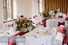 Rustic floral displays for wedding reception. The table arrangements composed of nude roses, red roses and spray pink roses and garden foliage. Rustic wedding, English wedding.