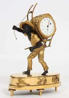 """PETITE PENDULE """"AU COLPORTEUR"""" En bronze doré et à patine brune, représentant un jeune noir marc"""
