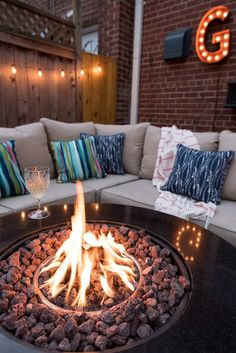 Usher in summer with family and friends gathered around the fire pit. Comfortable seating, string lights, and bright, patterned pillows make this patio prime for entertaining. Don't miss every stylish detail of this posh patio makeover from Simple Stylings.