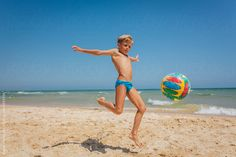 Boy playing with ball at the beach by MelkiN | Stocksy United