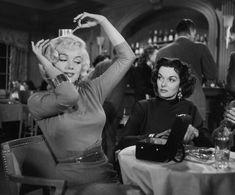 Marilyn Monroe balancing something on her head, with Jane Russell, in GENTLEMEN PREFER BLONDES.