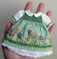 What an elaborately embroidered and smocked doll dress! So cute!