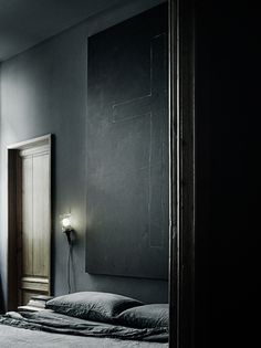 Wooden door, grey pillows, black wall, light Great mood with dark colors.