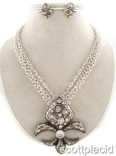 "CHUNKY 3.10"" LONG METAL FLEUR DE LIS PENDANT SILVER TONE NECKLACE SET WITH CRYSTAL ACCENTS    * If you need a necklace extender I have them for sale in my store.*         POST EARRINGS      NECKLACE: 16"" LONG + EXT       COLOR: SILVER TONE $21.99"