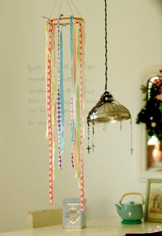 Maak een mobiel door aan een lampenkapringen allemaal kleurige linten in verschillende lengtes te knopen