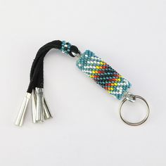 Carry your keys around in style! Navajo artist Charlene Jackson hand beaded this beautiful key ring. Great colors and patterns. 6 1/2″ x 5/8″ x 5/8″ Artist card included