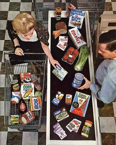 At the supermarket checkout, 1964. Processed food galore!