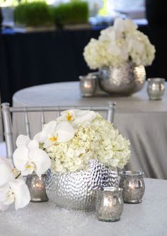 A low, simple, and elegant arrangement, using white phalaenopsis orchids, and white hydrangea, in a textured silver vase, surrounded by silver mercury glass votives. This picture was taken at, the Old Ursuline Convent in New Orleans, French Quarter.