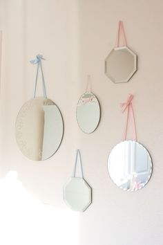 DIY Pottery Barn Kids mirror decor. purchased mirrors individually for about $2 ea. from Michael's arts & craft store, then simply hot glued ribbon onto the back of the mirrors and hung. Took no more than 40 min to do!