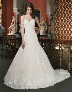 Justin Alexander wedding dresses style 8701 Beaded and corded lace appliques over a sequined lining on this A-line  gown that features a sweetheart neckline. Gown is finished with corded  hem lace and chapel length train. Style has regal satin buttons over the  back zipper.