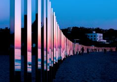 """The latest outdoor installation by American artist Phillip K. Smith III is a gorgeous line of mirrored poles stretching a quarter mile down Laguna Beach. The mirrored sculpture reflects the natural beauty of changing tides.  """"250 stainless steel posts, polished to a mirrored sheen, were spaced evenly in a gentle arc along the coastline. Over a period of 4 days, curious beach goers and art lovers discovered how the light and color of sand and surf illuminated the poles.""""  Photos: Lan..."""