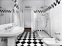 Black and white bathroom with extensive white tiling offset with black and white checkered strip on top of wall and on the floor