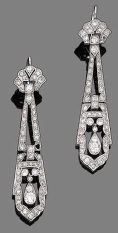 A pair of art deco diamond pendant earrings, circa 1925 Each fan-shaped surmount suspending an elongated openwork plaque with pear-shaped swing-drop, millegrain-set throughout with single and old brilliant-cut diamonds, diamonds approx. 3.10cts total, one diamond deficient, length 5.0cm.