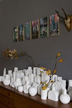 All white German porcelain displayed en mass against a darker background and accented by colorful art above.